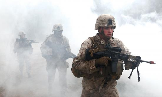 U.S. Marines with Fox Company, Battalion Landing Team 2/6, 26th Marine Expeditionary Force, use a smoke grenade to screen their movement as they prepare to enter a building during military operations in urban terrain (MOUT) training at Fort Pickett, Va., April 11, 2015