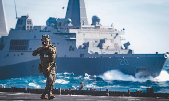 A Force Reconnaissance Marine with the 31st Marine Expeditionary Unit (MEU) clears the flight deck of the amphibious dock landing ship USS Ashland (LSD-48)