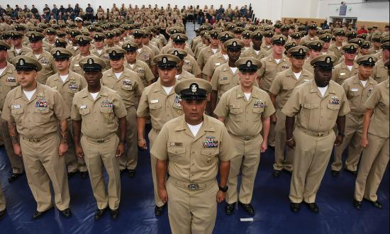 Members of Naval Station Mayport's Chief's Mess stand at attention during a Chief Petty Officer pinning ceremony at the base gy