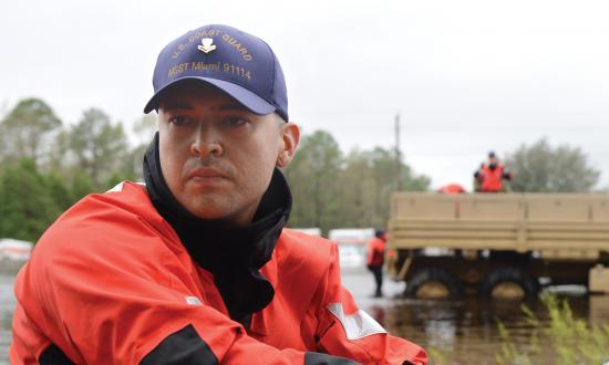 A member of Coast Guard Maritime Safety and Security Team Miami drives a shallow-water craft through floodwater caused by Hurricane Florence
