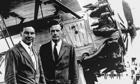 "Assistant Secretary David Ingalls, left, and aviation pioneer Charles Lindbergh stand in front of a U.S. Navy ""High Hat"" aircraft"