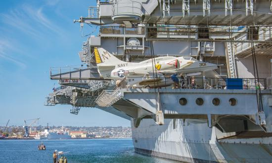 Museum-goers inspect the Midway's A-4F Skyhawk on the lowered aft side elevator, while active-duty sailors conduct small-boat drills in the  water below.