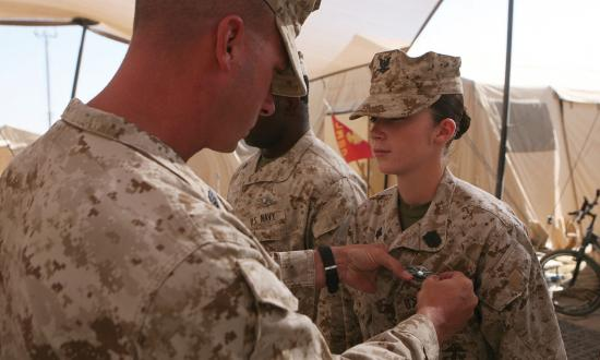 a Navy corpsman is presented with her Fleet Marine Force Warfare Specialist pin during a ceremony
