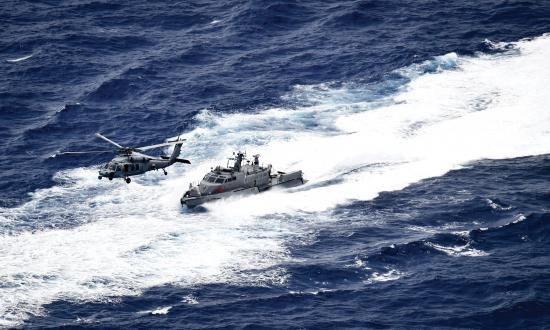 Aerial oblique view of a U.S. Navy Seahawk helicopter and a fast patrol boat