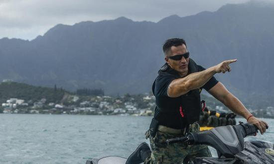 Marine gunnery sergeant directs his Marines from a jetski during a water rescue training event off the shore of Marine Corps Base Hawaii