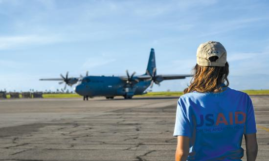 A USAID worker waits for a flight on a C-130J Hercules in Beira, Mozambique, April 3, 2019