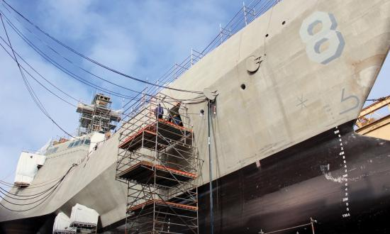 Shipyard workers in San Diego, California, perform upgrades on the forward mooring station of the littoral combat ship USS Montgomery (LCS-8).