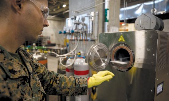 A Marine Corps corporal at Camp Kinser, Okinawa, places a 3-D printed part inside a sinter to bake and fuse.