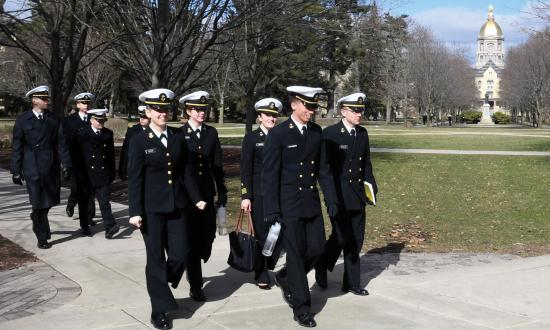 Naval Reserve Officers Training Corps (NROTC) midshipmen walk across the campus of the University of Notre Dame and past the iconic golden dome of the Basilica of the Sacred Heart