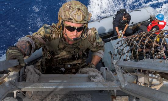 Coast Guard law enforcement detachments (LEDets) deploy with U.S. Navy strike groups as part of the Oceania Maritime Security Initiative. Here, a LEDet member climbs down to a rigid-hull inflatable boat to conduct a boarding mission.