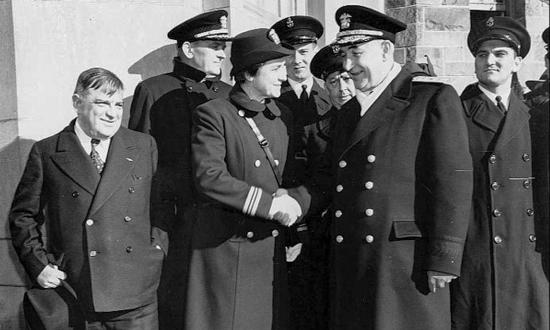 Lieutenant Commander Mildred McAfee shakes hands with Rear Admiral Randall Jacobs at a Female Officer Training School commissioning ceremony at New York City's Hunter College in early 1943.