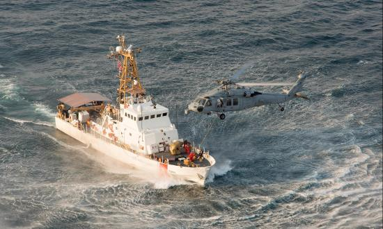 Aerial starboard bow view of USCGC Sapelo (WPB-1314) with a MH-60 Seahawk helicopter hovering over her bow.
