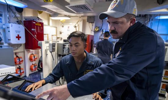 Hull Maintenance Technician First Class Benjamin Cascario, right, trains Lieutenant (junior grade) Jason Punsalan on standing engineering officer of the watch on board the USS John P. Murtha (LPD-26).