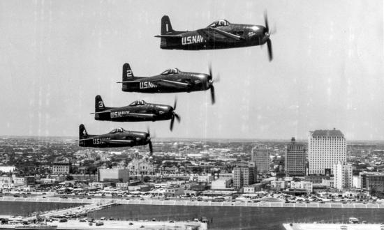 An aerial right side view of four F8F-1 Bearcat fighter aircraft in formation over Corpus Christi's water front area.