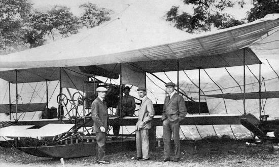 From left to right, Lieutenants T. G. Ellyson, J. H. Towers, and John Rodgers, USN stand in front of a Navy Curtiss Model E (A-1) Triad aircraft in Annapolis.