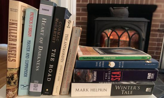 Books on a table by a fireplace