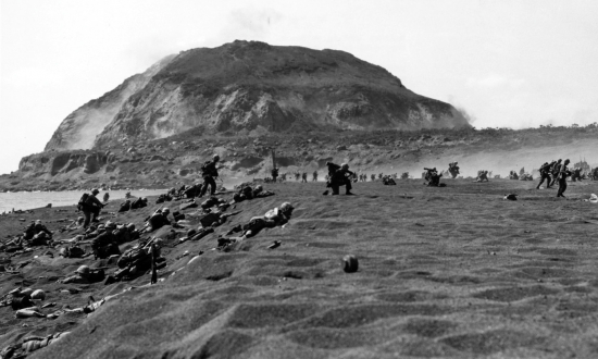 Marines advance in the shadow of Iwo Jima's Mount Suribachi